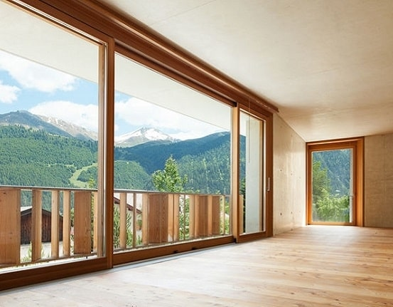 wooden sliding doors and windows installed in a design house with a view of a pinewood forest