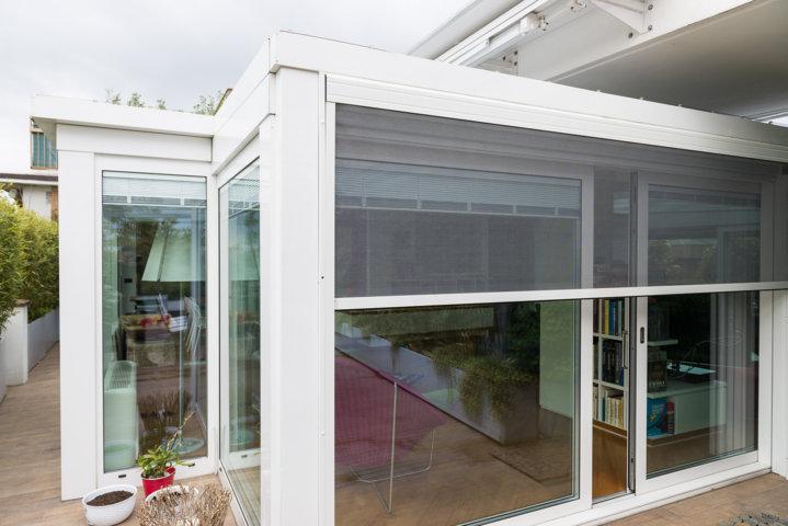 particolare di una veranda taglio termico in cui si vedono le zanzariere integrate e le veneziane motorizzate