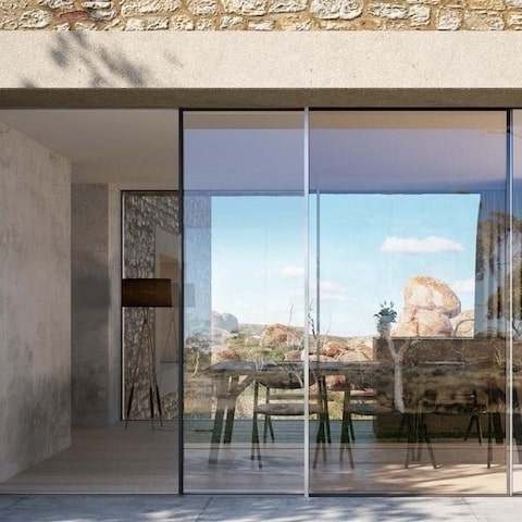 schuco panoramic sliding door installed in a renovated house with exposed stone wall